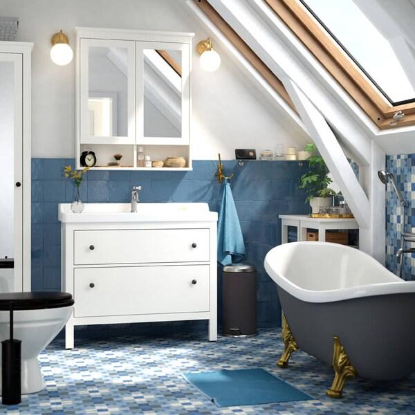 Kylpyhuone, jossa on siniset lattia- ja seinälaatat, vapaasti seisova kylpyamme ja valkoinen pesuallas.