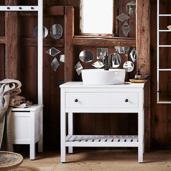 Kylpyhuone tummilla puuseinillä, peitetty pienillä ja eri muotoisilla peileillä ja valkoisilla HEMNES-kylpyhuonekalusteilla.