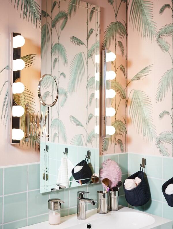 Kylpyhuoneen peili ja kohtisuora kylpyhuoneen valaisin sen kummallakin puolella. Vihreä ja vaaleanpunainen kylpyhuone, jossa on viidakkotapetti, tihkuu tunnelmaa.