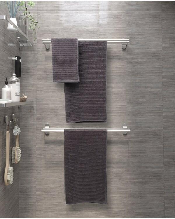 Kylpyhuoneen seinällä on harmaita pyyhkeitä ripustettuna kahdelle pyyhetangolle.