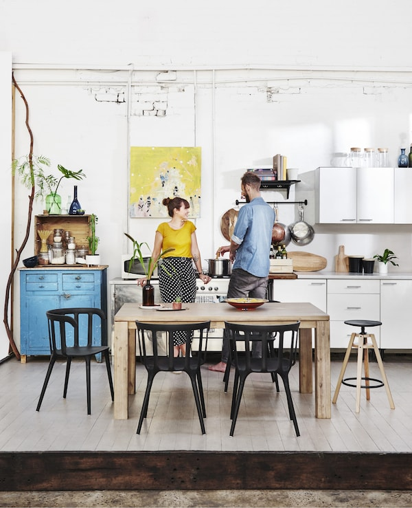 Kyra and Dave in their white kitchen with a wooden dining table and black chairs.