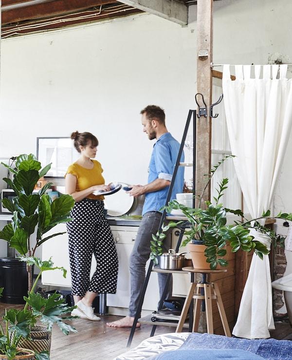 Kyra und Dave trocknen in ihrer Küche ab, u. a. mit INGEFÄRA Blumentopf mit Untersetzer für draußen/Terrakotta.