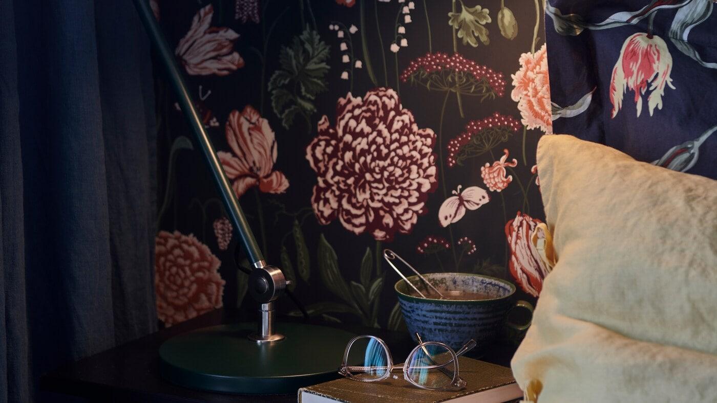 La base d'une lampe de travail ARÖD, une tasse et un livre avec une paire de lunettes sont placés sur une table de chevet.