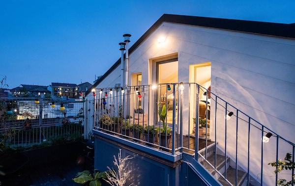 La casa vista da fuori, con la facciata con tetto a punta e il balconcino. Dentro le luci sono accese e si sente atmosfera di casa. La porta è aperta…