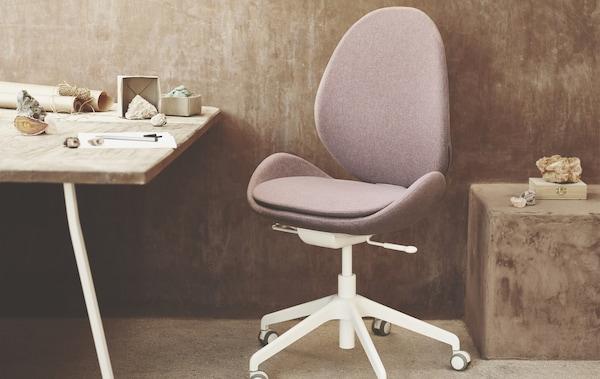 La chaise de bureau HATTEFJÄLL rose et blanche installée dans un bureau.