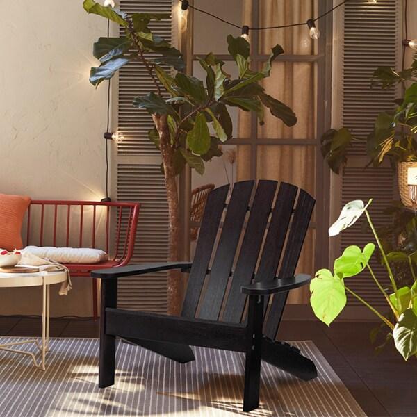 La chaise de terrasse noire KLÖVEN dans un espace extérieur avec une chaise rouge et de nombreuses plantes en arrière-plan.