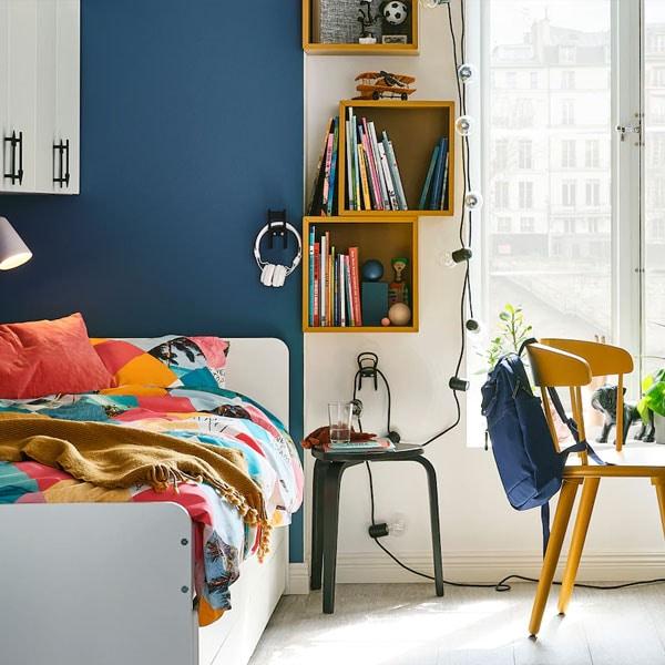 La chambre d'un enfant plus âgé avec une armoire-penderie SMÅSTAD et un lit SLÄKT en face d'une chaise OMTÄNKSAM et d'un bureau MICKE blanc.