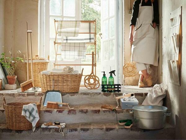 La collection de produits BORSTAD est posée dans une entrée ensoleillée alors qu'une femme tenant une tapette à tapis se trouve à côté.
