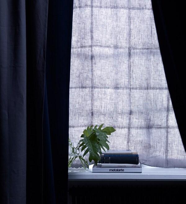 La combinación de una cortina acolchada y un estor de color azul oscuro en las ventanas evita la entrada de luz y el ruido.