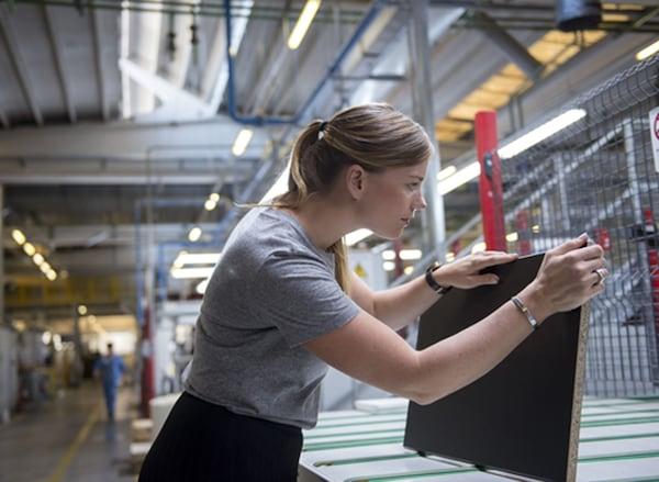 La développeuse produit Anna Granath tenant en main une façade de cuisine noire dans une usine.