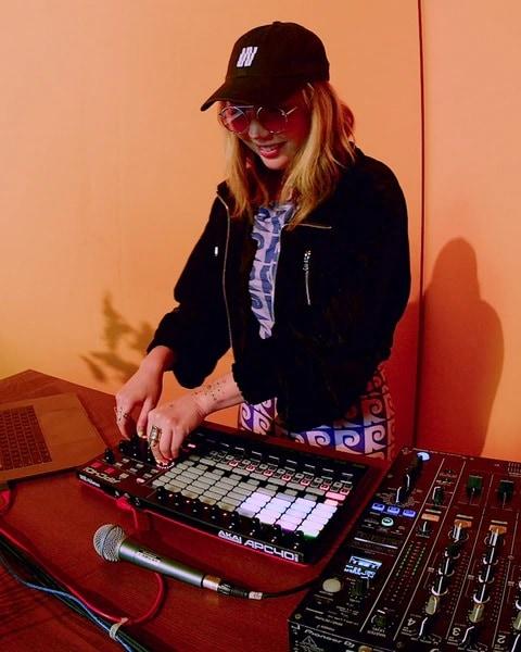 La DJ TOKiMONSTA derrière sa console de mixage, portant une veste noire et une casquette.