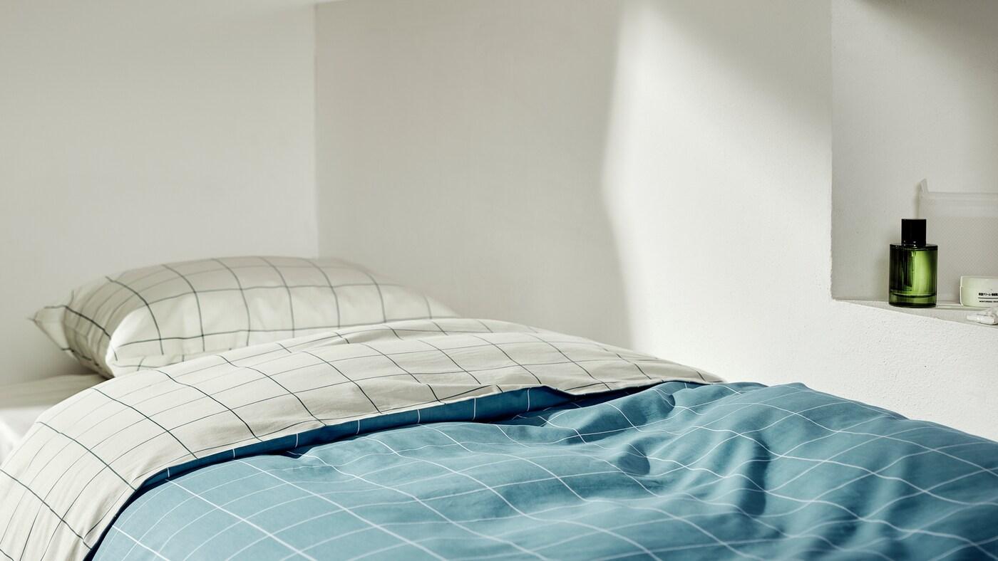 La housse de couette VITKLÖVER est mise en valeur sur un lit une place, avec le haut replié pour montrer les deux couleurs de base différentes de chaque côté.