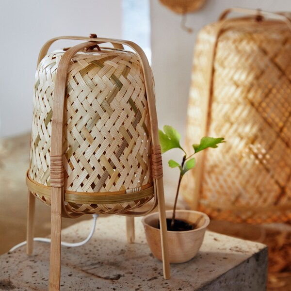 La lampada da tavolo KNIXHULT ha quattro gambe in legno curvato che racchiudono il paralume cilindrico in bambù intrecciato – IKEA