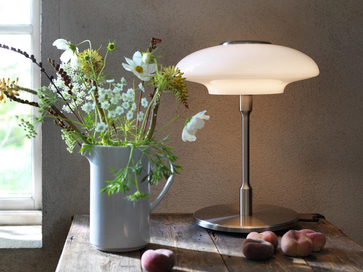 La lampe de table TÄLLBYN conçue dans un esprit Art Déco posée sur une table en bois à côté de quelques pêches et d'une cruche remplie de fleurs.