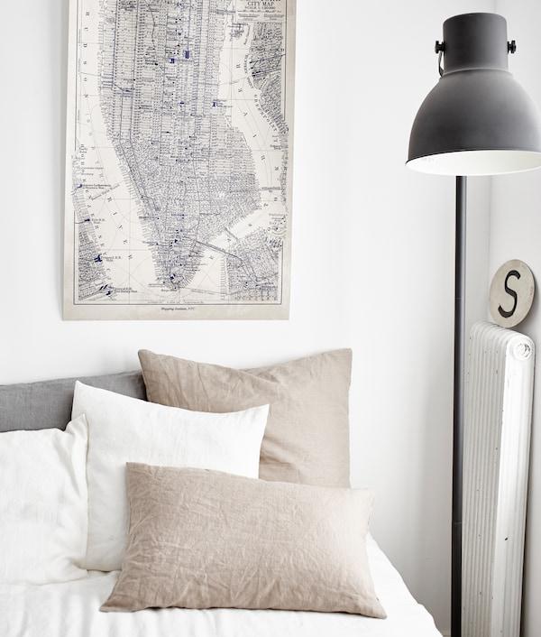 La paleta neutra de blancos y beige de esta ropa de cama ayuda a mantener un espacio tranquilo de trabajo/doméstico mezclado.