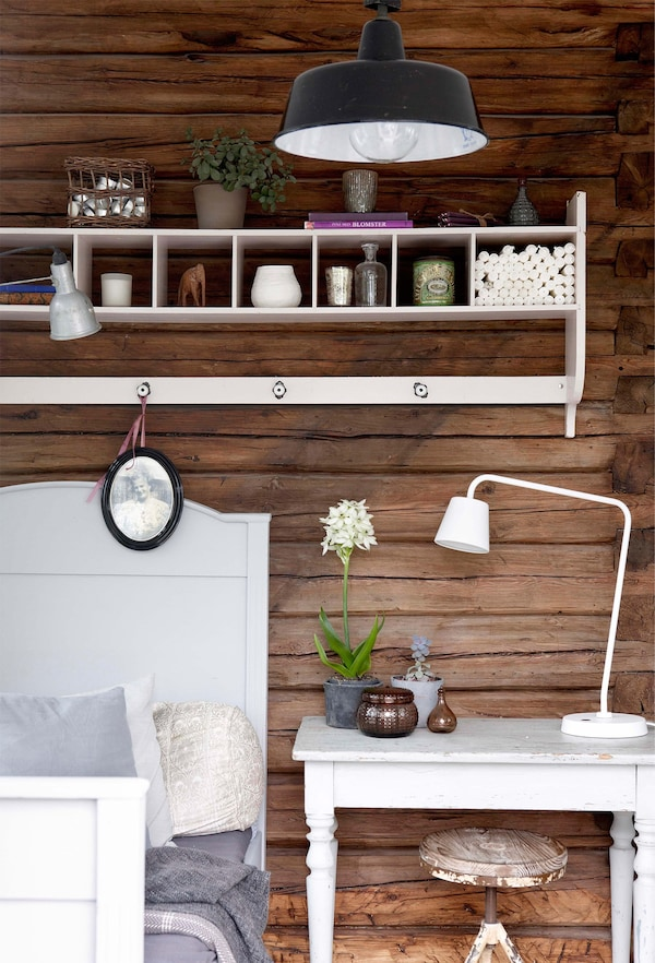 La pared de madera teñida de color oscuro es un fondo muy vistoso para los muebles blancos del dormitorio.