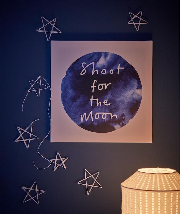 La parete sopra a una scrivania decorata con la canvas PJÄTTERYD ispirata alla luna e stelle disegnate con nastri e chiodi - IKEA