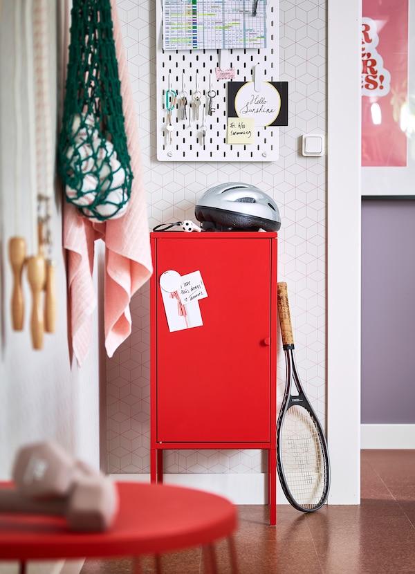 La puerta del armario estrecho IKEA LIXHULT en metal rojo es magnética, así que puedes colgar notas o recordatorios. Dentro tiene una balda, y en el interior de la puerta hay una barra para guardar cuadernos y otros artículos finos.