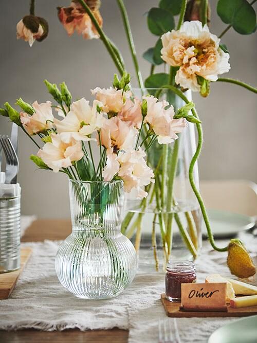 La section d'une table festive avec des fleurs colorées placées dans des vases en verre transparent PÅDRAG et BERÄKNA qui sont côte à côte.