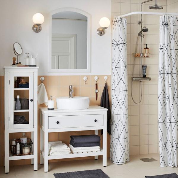 La série IKEA HEMNES pour salle de bain comprend des meubles de style traditionnel caractérisés par des tiroirs blancs, des porte-serviettes, des bancs et des vitrines, conçus pour s'intégrer dans un grand nombre d'espaces.