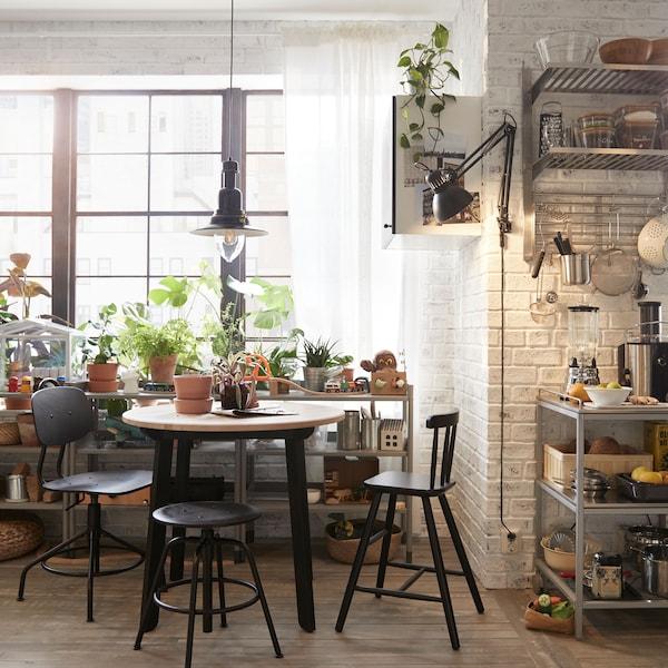 La table à manger IKEA GAMLARED a des pieds noirs et et un plateau rond en bois.