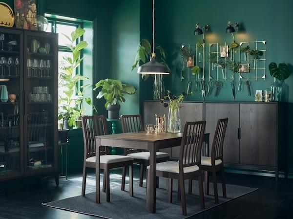 La table extensible et les chaises EKEDALEN dans une salle à manger avec murs verts et de nombreuses plantes.