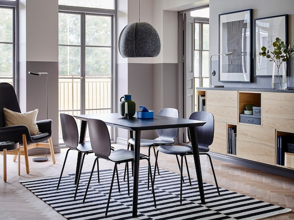 La table LISABO et les chaises SVENBERTIL, rapides à monter forment un ensembl élégant au centre de cette pièce dont le moitié inférieure du mur est peinte en gris et l'autre en blanc, half white walls and open and closed storage in ash.