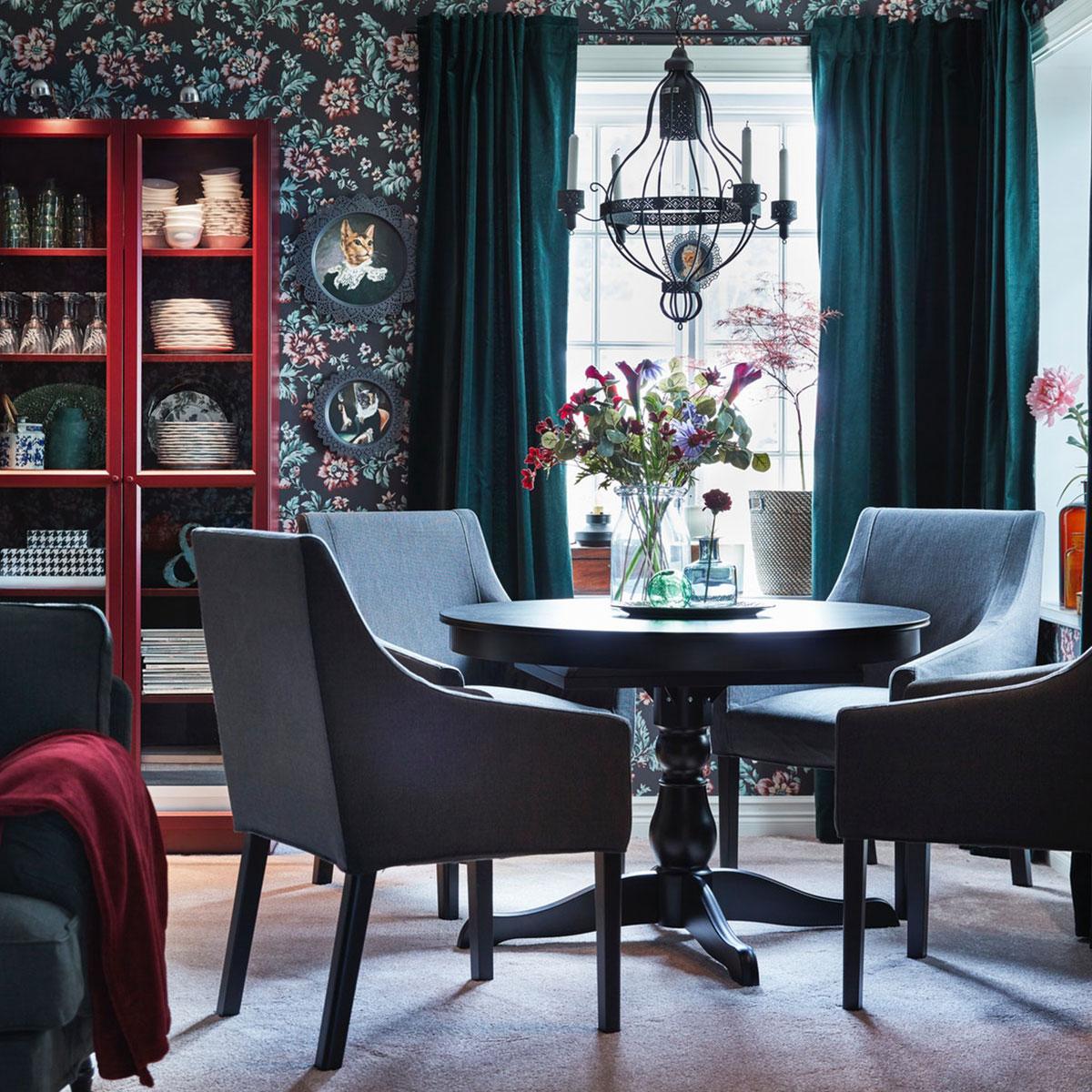 La table ronde extensible IKEA INGATORP noire et les chaises de salle à manger SAKARIAS en gris et à motifs floraux complètent le papier peint à motif floral vintage et les rideaux en velours vert foncé.
