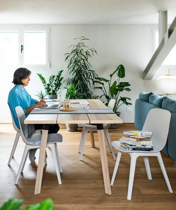 La zona pranzo, con tavolo, sedie e le piante sullo sfondo