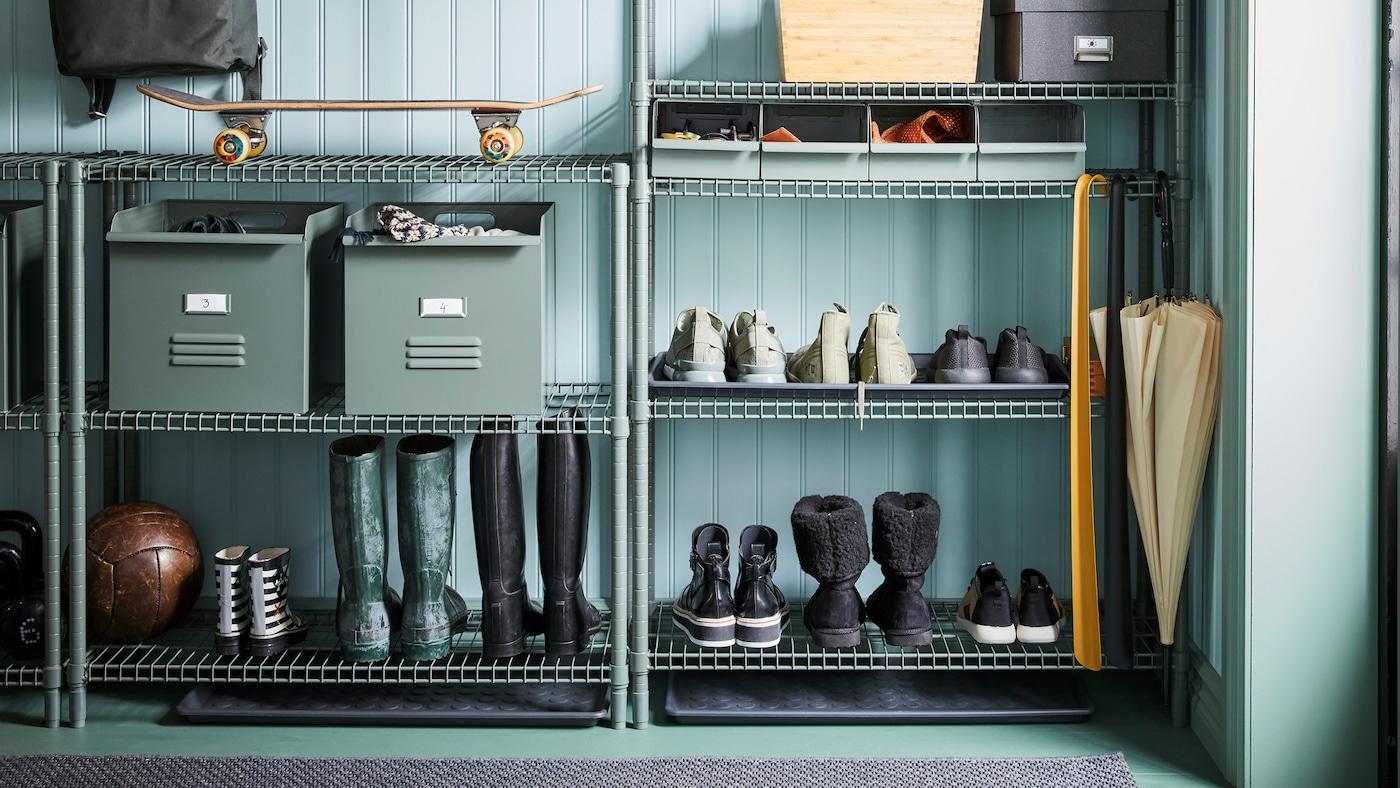 Laarzen, schoenen, metalen REJSA dozen, schoenlepels, een skateboard en andere spullen zijn opgeborgen op OMAR rekken in een hal.