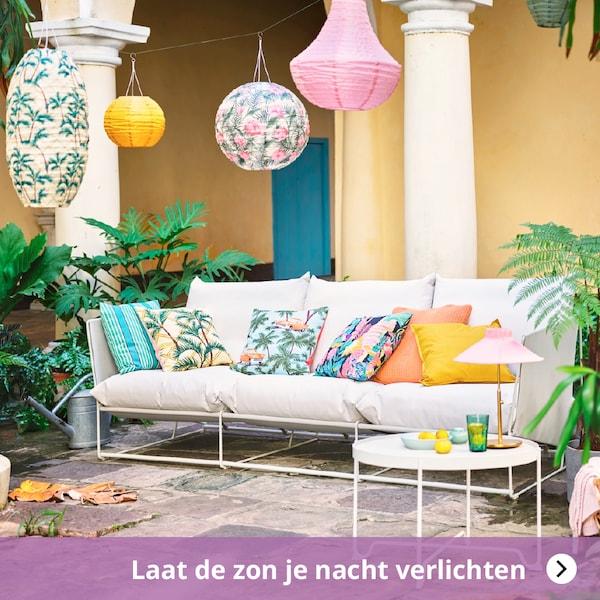 Laat de zon je nacht verlichten, tuinzetel met kleurrijke kussens en tuinverlichting