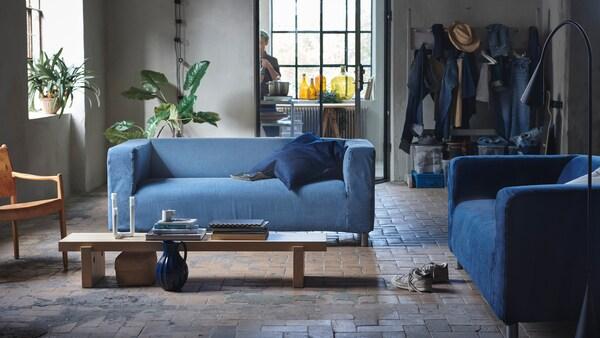 Laatoitetun olohuoneen lattialla on kaksi sinistä sohvaa. keskellä kapea puupöytä ja takana viherkasveja.