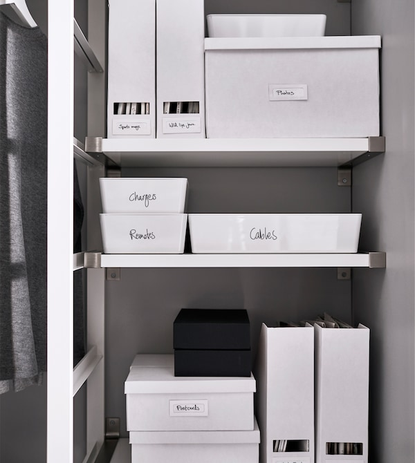 Labeled boxes and magazine holders keep things organised on a shelf.