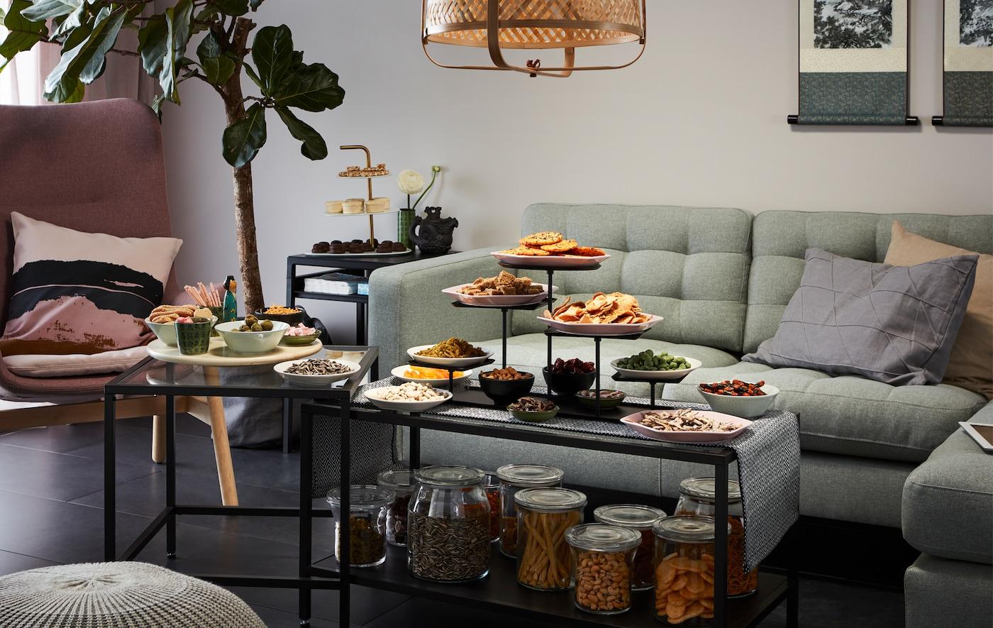 Lado del salón con sofá de esquina y sillón; en primer plano, un juego de mesas nido repletas de aperitivos, tanto envasados como servidos.