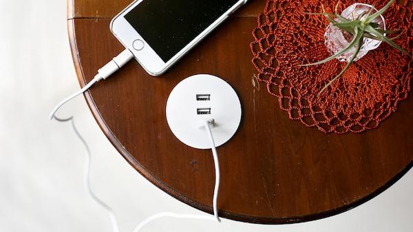 Ładowarka USB NORDMÄRKE zamontowana w blacie okrągłego drewnianego stolika. Do ładowarki za pomocą przewodu podłączony jest smartfon.