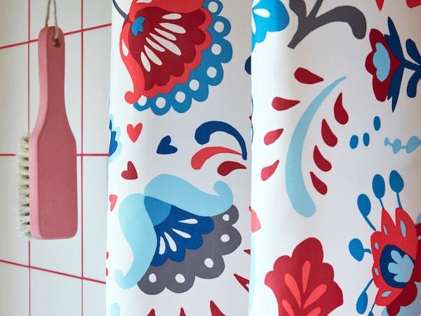Lähikuva IKEA KRATTEN suihkuverhosta, jossa on perinteinen skandinaavinen kukkakuvio monissa väreissä.
