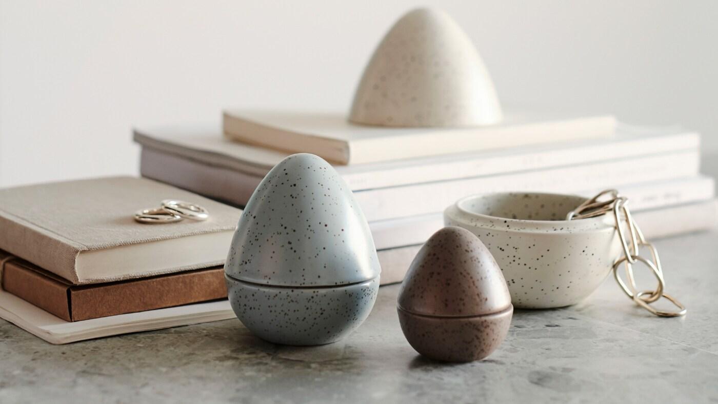 Lähikuva kolmesta RÅDFRÅGA koristemunasta, joiden takana on kirjoja. Yksi muna on auki, ja sen sisällä on koruja.