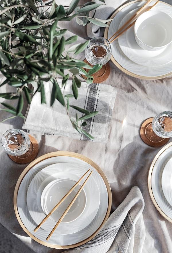 Lähikuva kynttilänjalka valkoista posliinia. Oliivin oksat näkyvät ja pöytä on peitetty VARDAGEN pöytäliinalla.