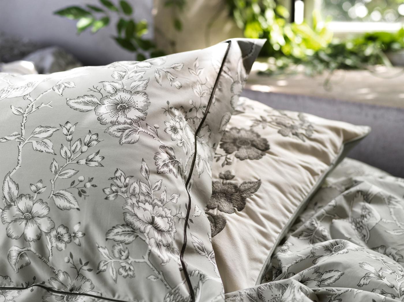 Lähikuvassa harmaa kukkakuvioinen PRAKTBRÄCKA pussilakana ja tyynyliina, jossa on perinteisiä kukkakuvioita mustalla ja valkoisella.
