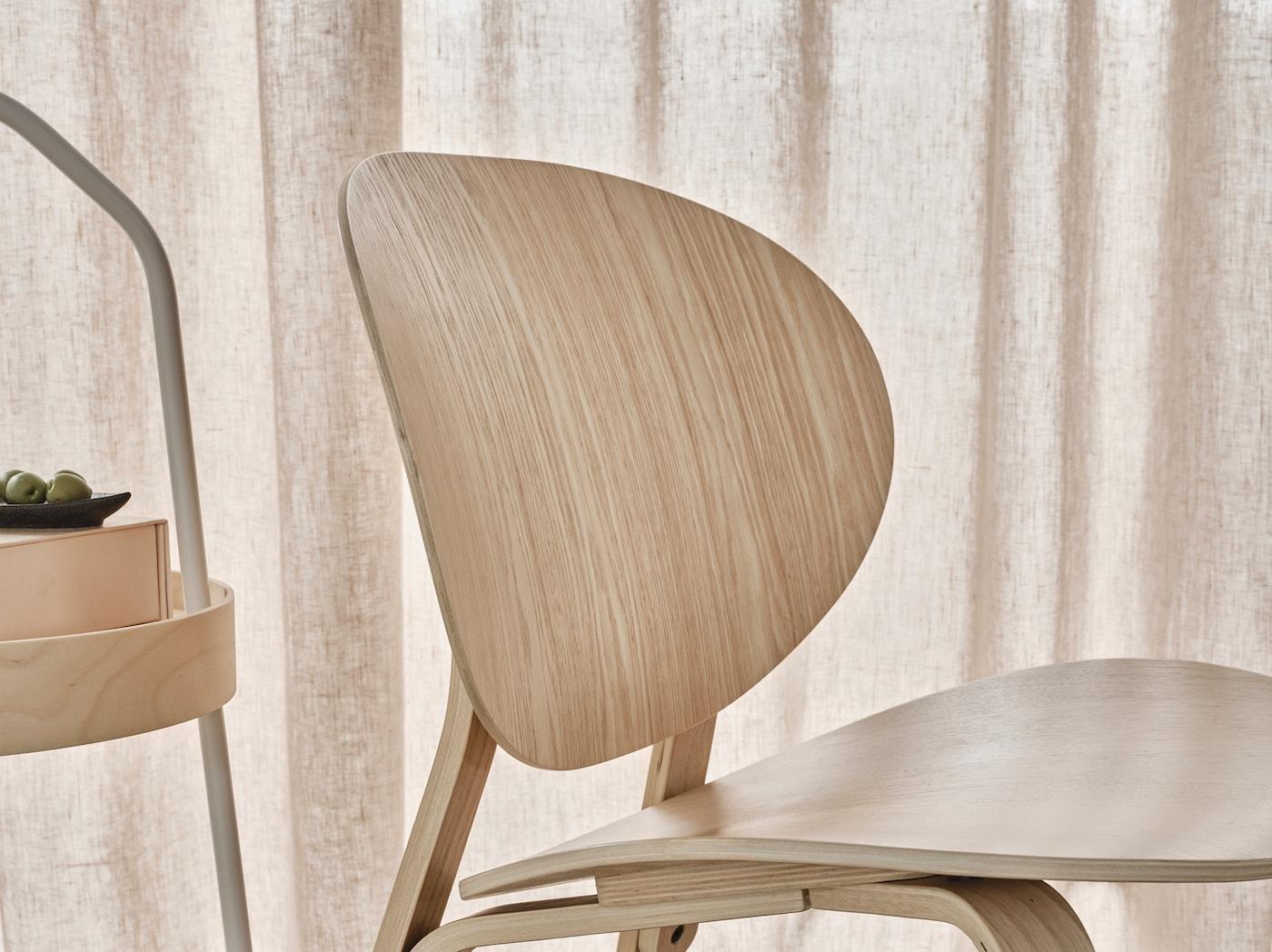 Lähikuvassa vaaleaksi petsatusta tammiviilusta tehty FRÖSET-lepotuoli, jonka muotoilu on modernin skandinaavinen ja keveä.
