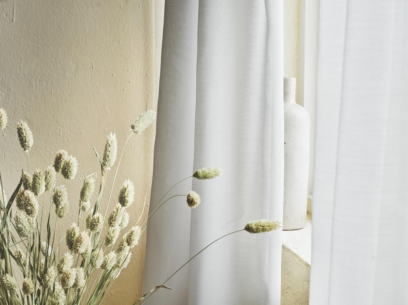 Lähikuvassa valkoiset GUNRID ilmanpuhdistusverhot, jotka roikkuvat ikkunan vieressä kuivattujen viljantähkien vieressä.