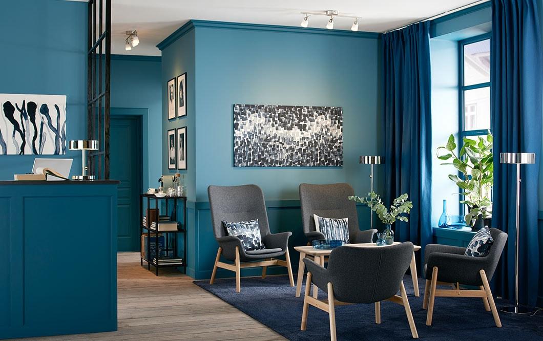 Lämmintä tunnelmaa toimistoon. Tunnelmallinen valaistus ja virkeät värit luovat ilmapiirin paremmille palavereille. Harmaa IKEA VEDBO-lepotuoli.
