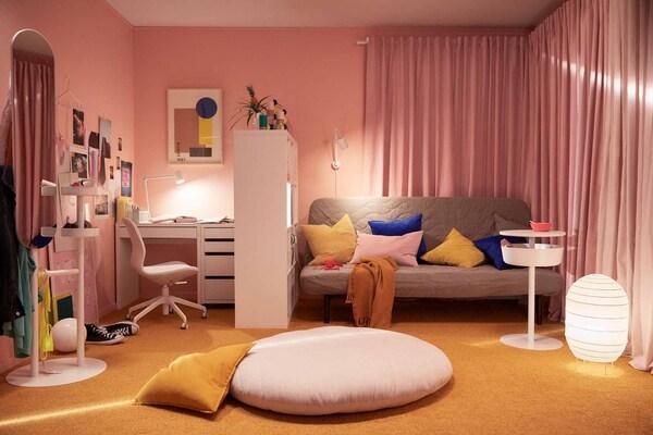 Lämmintunnelmainen huone, jossa huonekasvit, valo ja tekstiilit luovat kotoisan ympäristön.