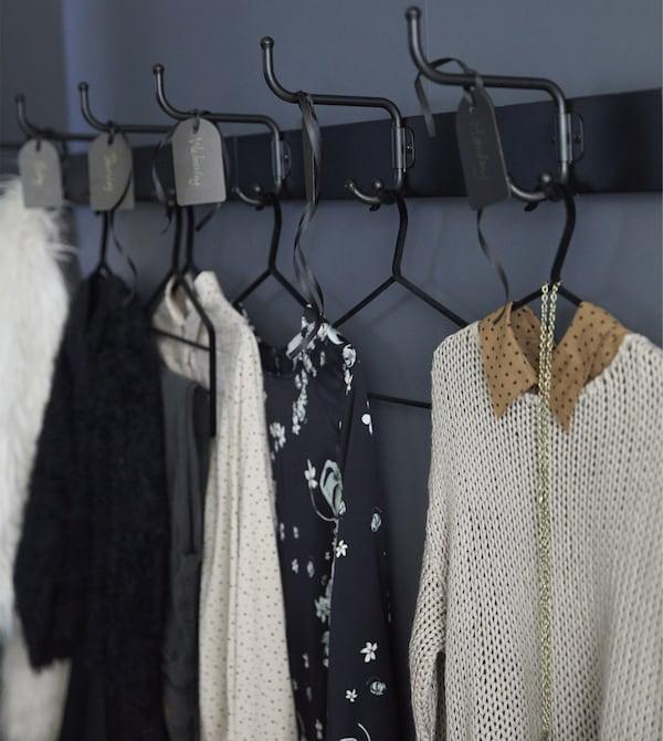 لأفكار تخزين الملابس، جرب استخدام علاقات مثل PINNING من ايكيا. ضع بعضها بقرب دولاب الملابس لتستطيع التخطيط للملابس التي سترتديها وتوفير الوقت في الصباح. وضعنا علاقتين مغطاتين باللون الأسود مع ثلاث علاقات بجانب بعضها البعض بحيث تكفي للتحضير لمدة أسبوع.