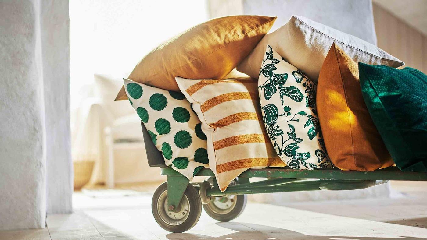 Lajitelma tyynyjä kevään väreissä asetettuna vihreään kärryyn.
