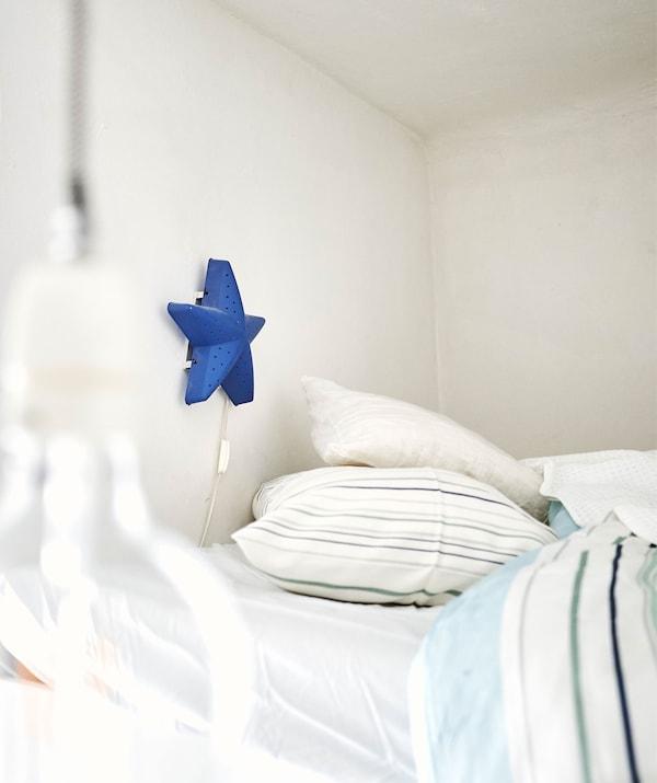 Lampă albastră în formă de stea pe un perete deasupra unui pat cu materiale textile cu imprimeuri.
