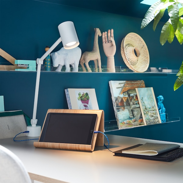 Lampa biurkowa NYMÅNE oświetlająca tablet ułożony na podstawce i zasilający go kabel podłączony do gniazda USB w lampie.