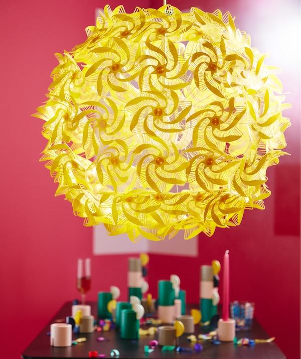 Lampă suspendată galbenă și mare, realizată din spirale inspirate de origami, conectată la o formă rotundă, emițând o lumină difuză într-o încăpere roșie.