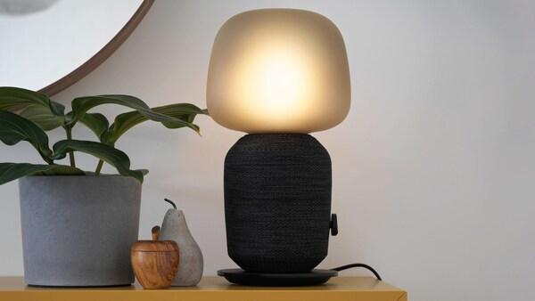 Lampa Symfonisk s reproduktorom, dekorácia v tvare jablka a hrušky a kvetináč na polici.