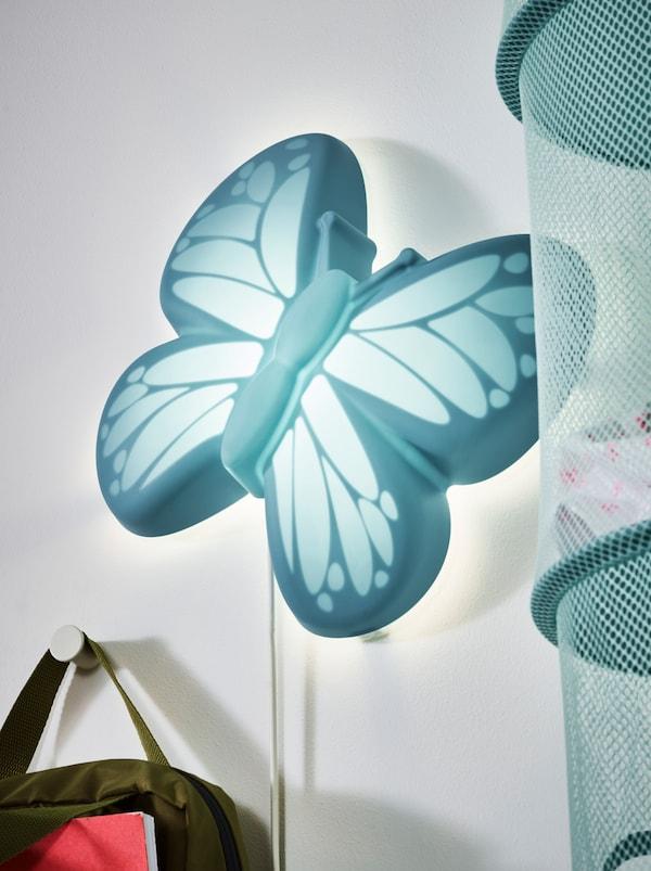 Lampada da parete a LED UPPLYST turchese, a forma di farfalla, tra una borsa appesa a un gancio e un portatutto pensile in rete.